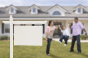 Blank Real Estate Sign and Playful Hispanic Family in Front of House.